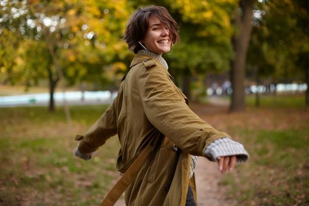 Buiten foto van jonge mooie blij bruinharige vrouw met kort kapsel gelukkig lachen terwijl staande boven wazig park in warme stijlvolle kleding