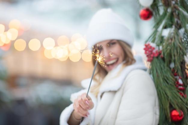 Buiten foto van jonge mooie gelukkig lachend meisje met sparkler, wandelen op straat. vrouw stijlvolle winterkleren dragen. kerstmis, nieuwjaar, concept.