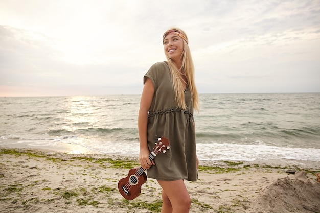 Buiten foto van jonge mooie witharige vrouw gekleed in zomerkleding ukelele te houden en wijd te glimlachen terwijl opzij kijkt, geïsoleerd over zee