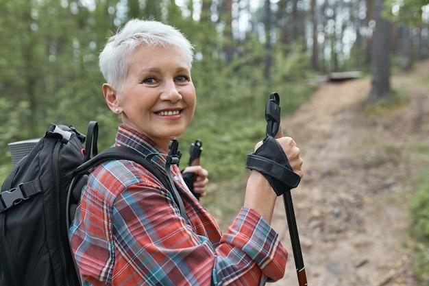 Buiten foto van mooie energieke volwassen vrouw met rugzak met behulp van stokken, genieten van nordic walking in het bos, camera kijken met een blije glimlach