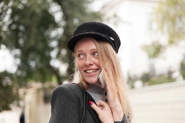 Buiten foto van mooie modieuze blonde jongedame met casual kapsel over haar schouder kijken en breed glimlachen terwijl het hebben van telefoongesprek