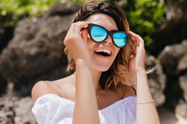 Buiten foto van schattige europese vrouw rondkijken met een glimlach. gelukkige vrouw in zonnebril plezier in het resort.