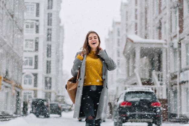 Buiten foto van sierlijke vrouwelijke model in trendy lange jas ontspannen in de stad in de winterdag. knappe jonge vrouw in gele trui met plezier tijdens het winkelen in de ochtend van december.