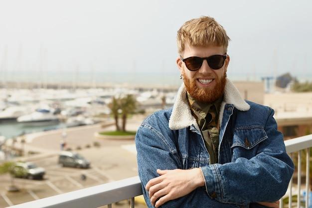 Buiten foto van vrolijke modieuze jonge europese man met lange gemberbaard