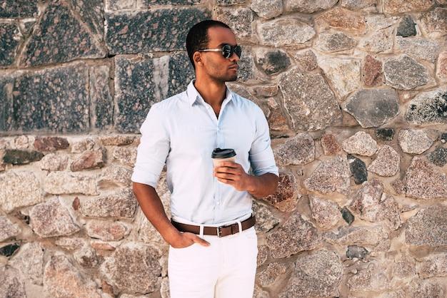 Buiten genieten van verse koffie. knappe jonge afrikaanse man in slimme vrijetijdskleding die een koffiekopje vasthoudt terwijl hij buiten tegen de gestenigde muur staat
