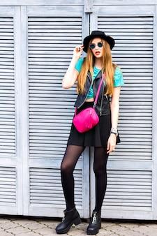 Buiten grunge mode portret van trendy hipster blonde vrouw, gelukkig positieve emoties, poseren op het stuur, heldere stijlvolle look, zonnebril, hoed, leren jas en over het lichaam tas.