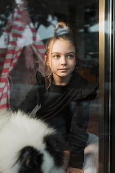 Buiten het raam kijken meisje en hond