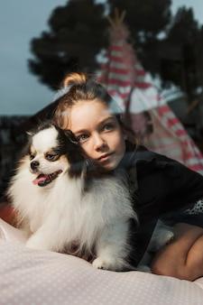 Buiten het raam kijken meisje en pluizige puppy