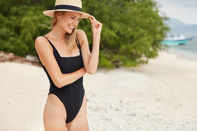 Buiten horizontaal portret van tevreden slanke vrouw met slanke benen, heeft gelukkig verlegen neerkijken, perfect figuur, draagt zwart zwempak, vormt tegen uitzicht op de oceaan. mensen, rust en recreatie concept