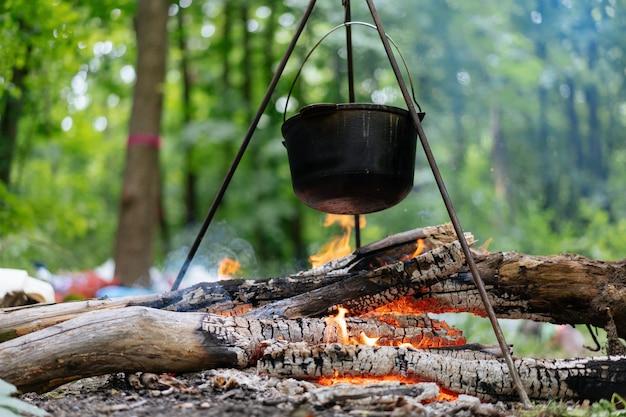 Buiten kamperen. kokende bolhoed op statief gehangen boven brandend vuur op de achtergrond van gras en afgebroken brandhout