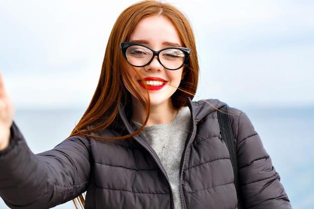 Buiten levensstijl beeld van vrolijke mailing gember vrouw selfie maken in de buurt van zee, koude winderig winterweer, positieve emoties.