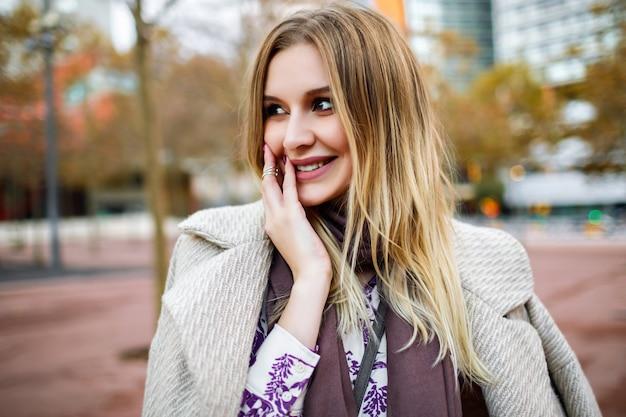 Buiten levensstijl positief portret van mooie blonde vrouw die lacht einde geniet van tijd, elegante outfit van de glamour, het dragen van jurk en jas, warme kleuren, lente herfst tijd.
