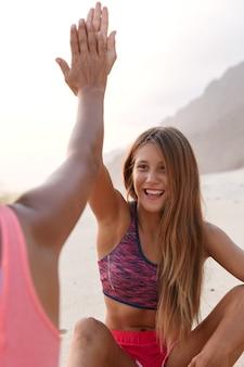 Buiten mening van gelukkig europees meisje geeft high five aan haar kameraad