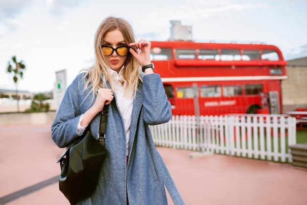 Buiten mode beeld van stijlvolle jonge vrouw poseren in london street, elegante casual zakelijke outfit, kus verzenden en kijken op camera, herfst lente midden seizoen tijd, getinte kleuren.