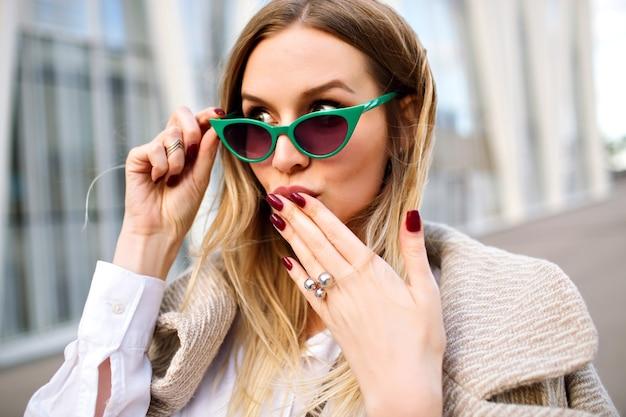 Buiten mode close-up portret van prachtige blonde zakelijke dame vrouw, glimlachend en kijkend op camera, kasjmier jas, vintage cat eye zonnebril, sieraden, zachte kleuren.