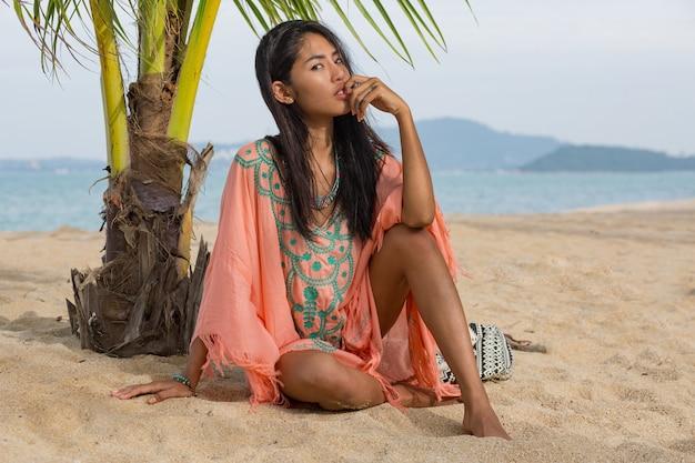 Buiten mode portret van aziatische vrouw op tropisch strand, ze is ontspannen, dromen. sieraden, armband en ketting dragen.