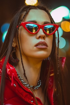 Buiten mode portret van glamour jonge vrouw met gevlochten haar draagt rode donsjack en mode rode zonnebril op neon straatverlichting