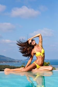 Buiten mode portret van jonge sexy model vrouw met perfect slank fit gebruind lichaam, geniet van haar zomervakantie. prachtig uitzicht op zwembad, eiland, oceaan en natuur, bikini en zonnebril dragen.