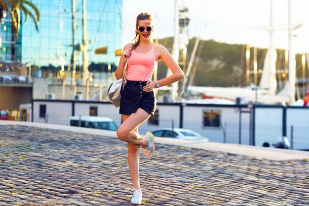 Buiten mode portret van jonge sportieve vrouw plezier reizen en wandelen bij luxe jachtclub, avondzonlicht, felle kleuren
