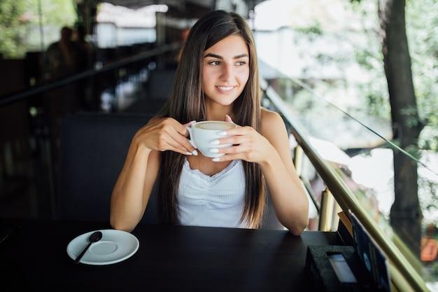 Buiten mode portret van mooi jong meisje thee koffie drinken
