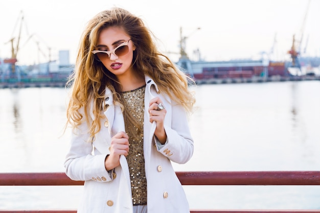 Buiten mode portret van verleidelijke sensuele mooie vrouw die zich voordeed op zeehaven in avondzonlicht, stijlvolle luxe gouden zonnebril en kasjmier jas dragen.