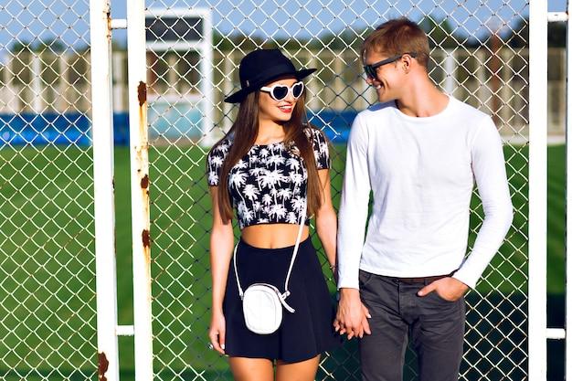 Buiten mode portret van verliefde paar knuffels op sportterrein, trendy zwart-witte kleding, vintage zonnebril, poseren op romantische date, zonnige dag, felle kleuren, liefde, relaties.