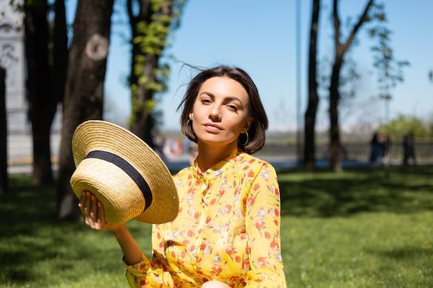 Buiten mode portret van vrouw in gele zomerjurk en hoed zittend op het gras in het park