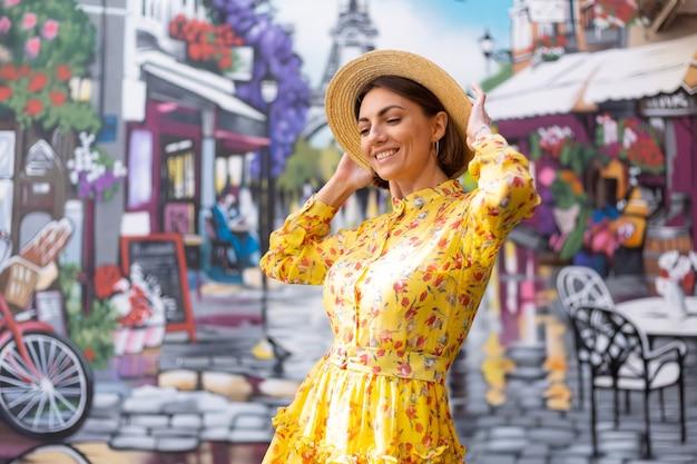 Buiten mode portret van vrouw in gele zomerjurk op straat kleurrijke muur