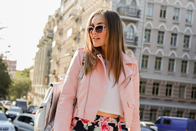 Buiten modieus portret van blonde vrouw die zich voordeed op straat. stijlvolle zonnebril, roze leren jas en rugzak dragen.