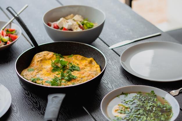 Buiten ontbijt garnalenomelet als ontbijt omelet in een koekenpan als ontbijt lunch voor een man gebakken omelet met groenten zomers eten op straat eiersoep regulier eten dieet bouillon