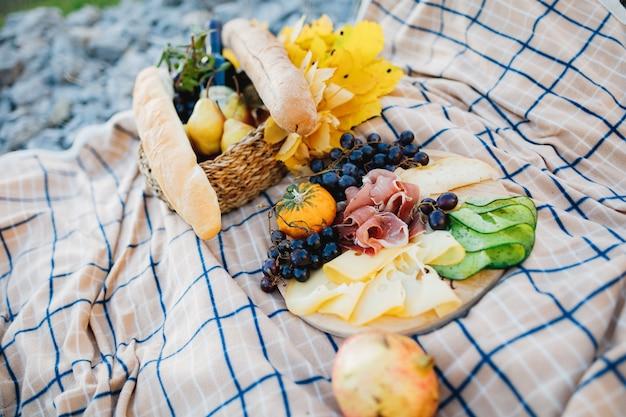 Buiten picknick met een bord vlees en kaas en druiven, een mand met een stokbrood en een fles