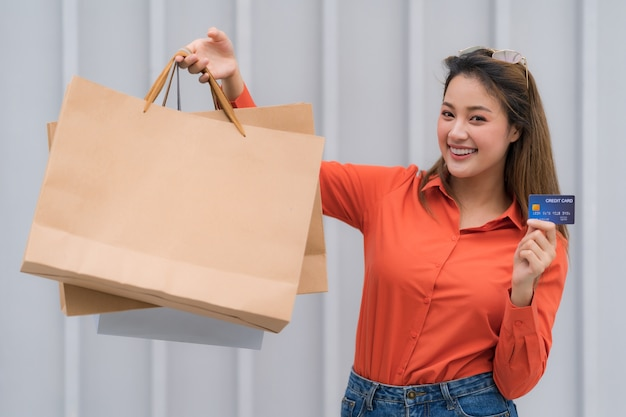 Buiten portret van gelukkige vrouw met boodschappentassen met creditcard