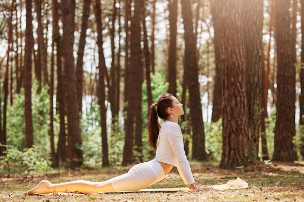 Buiten profiel portret van slanke vrouw die yoga beoefent in het bos, witte sportkleding kleedt, cobra pose doet op karemat in open lucht, recht vooruit kijkend