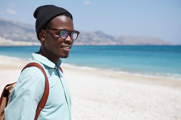 Buiten schot van aantrekkelijke gelukkige jonge afrikaanse reiziger met rugzak gekleed in stijlvolle kleding ontspannen op het woestijnstrand vroeg in de ochtend, overweegt kalme zee