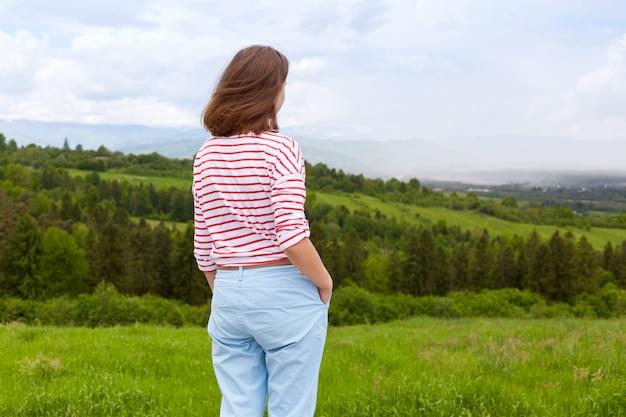 Buiten schot van aantrekkelijke jonge vrouw, gekleed in casual broeken en witte t-shirt met rode strepen