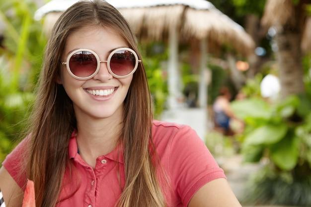 Buiten schot van aantrekkelijke jonge vrouw in modieuze ronde zonnebril met spiegel lenzen, gelukkig glimlachen, genieten van vrije tijd tijdens vakantie, zittend tegen groene bomen