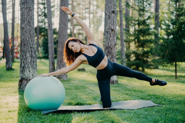Buiten schot van actieve brunette vrouw in sportkleding vormt op yoga mat, doet rekoefeningen met gymnsatic bal, poses in bos of park op groen gras.