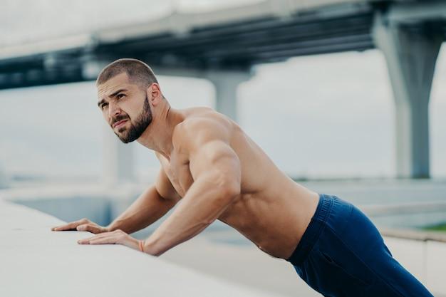 Buiten schot van bebaarde gespierde man doet push-up oefeningen opwarmt voor de training