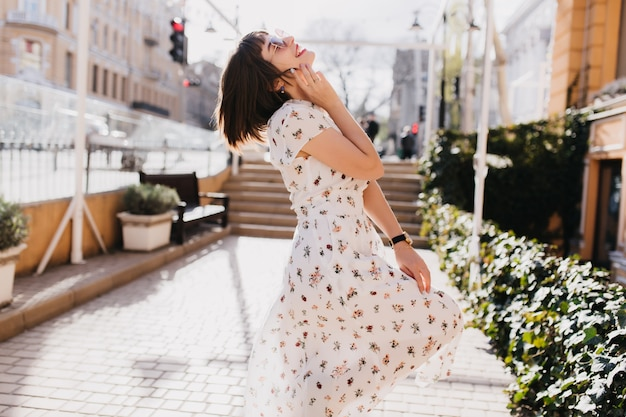 Buiten schot van bevallig meisje ontspannen in zonnige dag. stijlvolle kortharige dame in witte jurk dansen op straat.