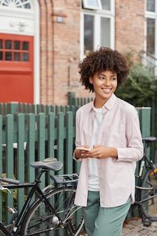 Buiten schot van donkere huid vrouwelijke blogger leest nieuwsfeed in sociale netwerken, poses in landelijke omgeving in de buurt van hek en fiets