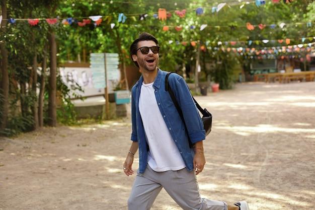 Buiten schot van gelukkig knappe jonge man met baard wandelen door groen stadspark op zonnige dag, wegkijken met een brede glimlach, het dragen van vrijetijdskleding