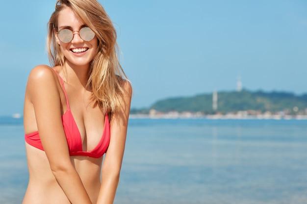 Buiten schot van gelukkig vrouwtje rust op zee, vormt tegen de prachtige oceaan of zeezicht met blauwe horizon, draagt trendy shases en rode bikini, wordt bruin op de kustlijn. zomertijd en vrije tijd.