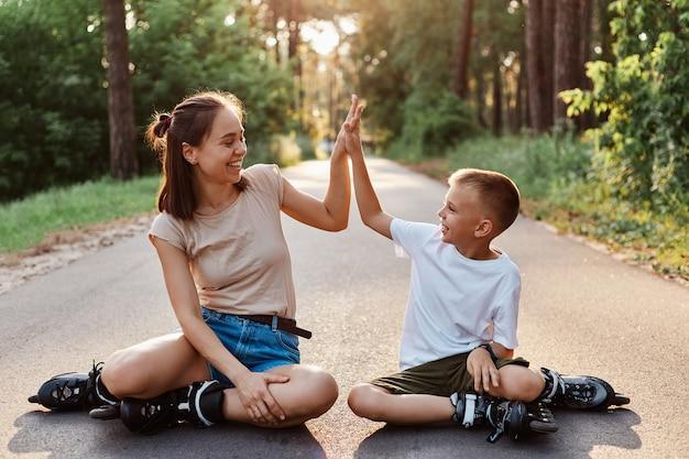 Buiten schot van gelukkige familie moeder en zoon dragen casual stijl kleding en rolschaatsen zittend op asfaltweg in park, jongen geven aan moeder high five, kijken elkaar met een glimlach.