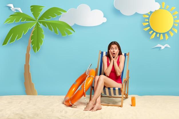 Buiten schot van geschokt vrouw zonnebaadt op strandstoel, gekleed in badpak