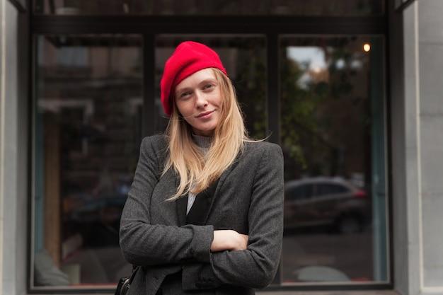 Buiten schot van jonge aantrekkelijke blonde vrouw in rode baret kruising handen op haar borst, licht kijken en glimlachen