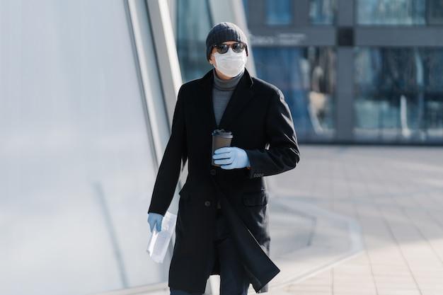 Buiten schot van jonge man in zwarte jas, steriel medisch masker en beschermende rubberen handschoenen, drinkt afhaalkoffie, houdt papieren vast, moet gaan werken in lege straat tijdens quarantaine, coronavirus