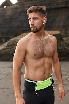Buiten schot van jonge mannelijke atleet voelt gezond, heeft een sportieve lichaamsvorm