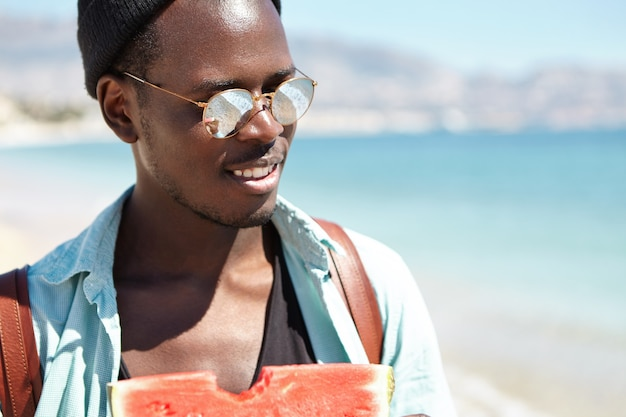 Buiten schot van jonge mannelijke toerist die van zoete verse watermeloen geniet