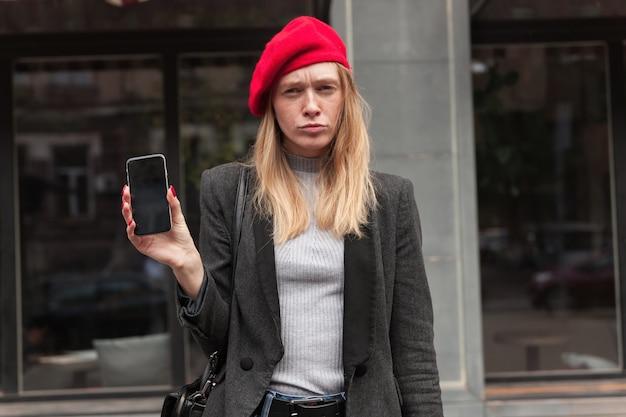 Buiten schot van jonge modieuze blonde langharige dame met haar mobiele telefoon en fronsen wenkbrauwen tijdens het kijken, staan