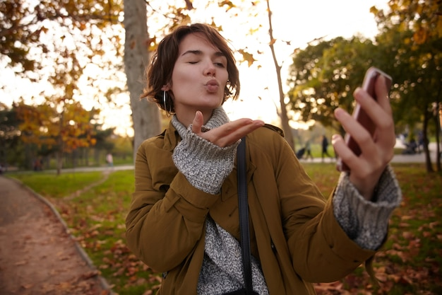 Buiten schot van jonge mooie bruinharige stijlvolle vrouw met casual kapsel verhogen haar handpalm terwijl blazen lucht kus van haar mobiele telefoon en knipogen met één oog